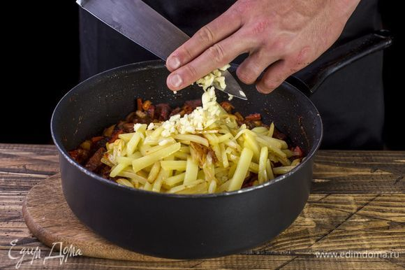 Почти готовый картофель переложите к мясу. Добавьте мелко нарубленный чеснок. Тушите еще пять минут.