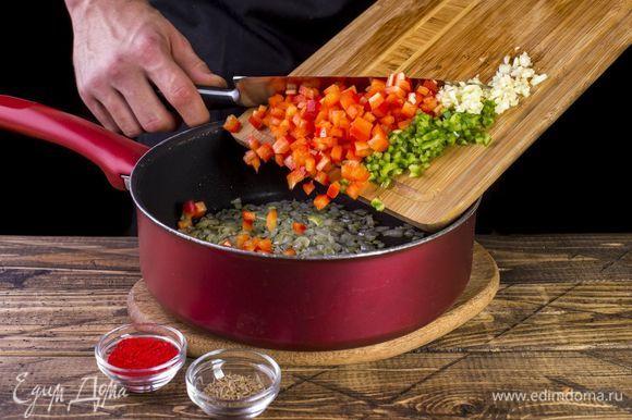 Обжарьте лук до мягкости, добавьте перец, чеснок, паприку и зиру. Тушите 5 минут, регулярно помешивая.