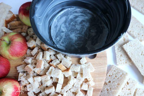 Обрезки хлеба разрежьте на небольшие кубики. Подсушите их в духовке при 180°C. Нам потребуется 1 горсть подсушенного хлеба. Перед выпеканием шарлотки надо сбрызнуть хлеб растопленным сливочным маслом (10 г). Борта формы обильно смазать сливочным маслом. Хорошо смазать маслом (15 г) бумагу для выпечки, которой следует застелить дно формы.