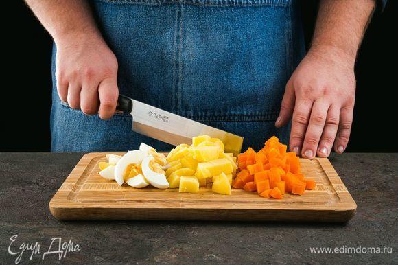 Отварите картофель, морковь и яйца. Нарежьте яйца дольками, овощи — кубиками.