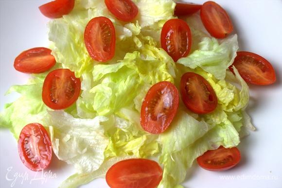 На тарелку порвать листья салата. Сверху кладем помидоры черри.