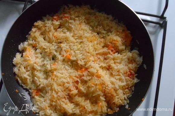 Добавить рис и жарить, пока не выпарится вода.
