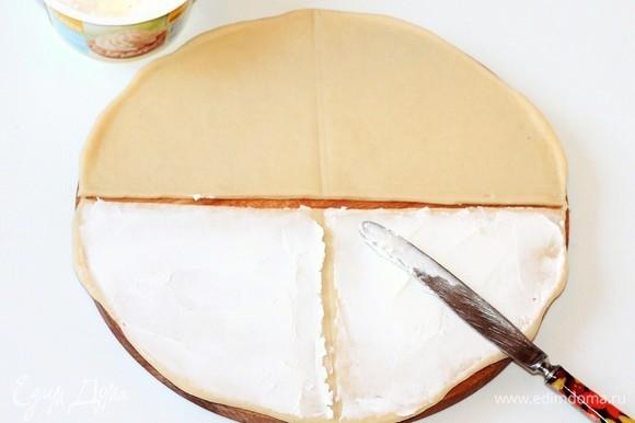 Разделить каждый круг пополам. В каждой половинке круга отметить (но не резать) середину. Смазать половинки круга творожным сыром.