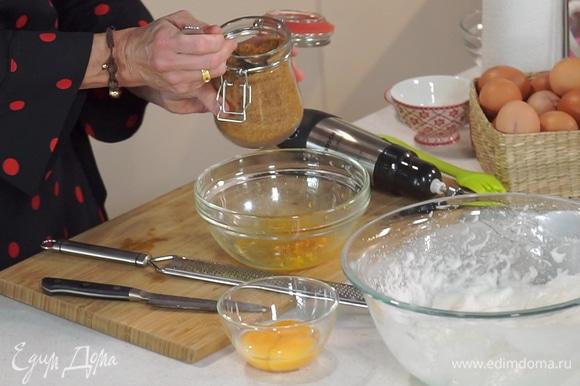 С апельсина снять цедру, выжать сок, перемешать и добавить 1 ст. л. коричневого сахара. По одному ввести желтки, каждый раз взбивая смесь на медленной скорости.