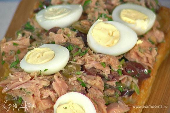 На одну часть чиабатты выложить салат с тунцом, перепелиные яйца, нарезанные дольки помидора и пару анчоусов. Накрыть сверху второй частью хлеба.