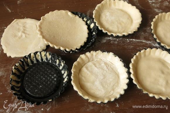 На 6 тарталеток вырезаем круги из теста и выкладываем в смазанные формы. Протыкаем вилкой.