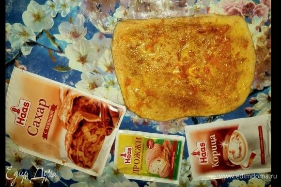 После того как тесто поднимется, разделить его на несколько частей. Каждую часть раскатать в прямоугольник, подготовленный пласт теста смазать желтком, обильно посыпать корицей с сахаром Haas и натереть сверху цедру апельсина.
