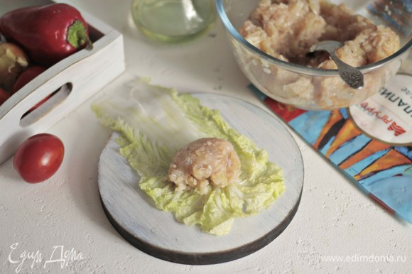 Острым ножом срезаем толстое основание у листьев салата. На край выкладываем фарш и заворачиваем по типу конвертика.