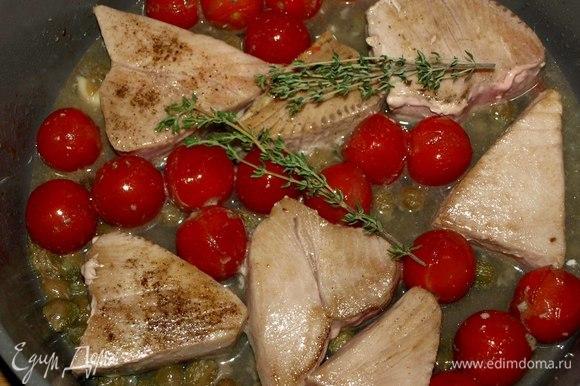 На чистой сковороде разогреваем оливковое масло. Зубчик чеснока разрезаем на 4 части. Обжариваем 2 минуты помидоры черри, каперсы, чеснок, анчоусы. Добавляем вино, доводим до кипения. Добавляем тунец и тимьян, тушим несколько минут под крышкой до необходимой для вас готовности рыбы. Снимаем с огня и даем отдохнуть 1–2 минуты. Выкладываем на тарелку и подаем.