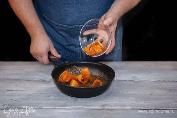 Хурму нарежьте крупными дольками, добавьте в сковороду, жарьте 1 минуту.