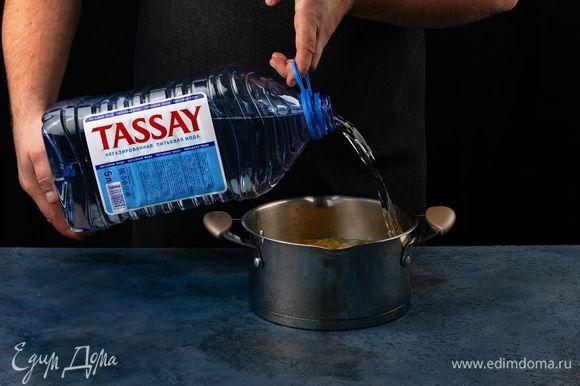 Залейте водой Tassay. Добавьте в кастрюлю фасоль и тертые помидоры.
