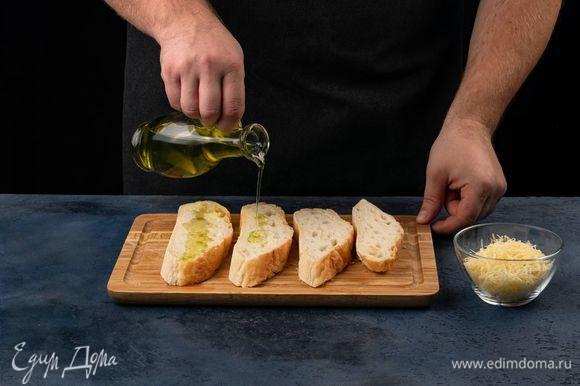 Сыр натрите на крупной терке. Хлеб нарежьте на ломтики, полейте оливковым маслом.