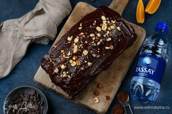 Чуть остывший кекс полейте глазурью, посыпьте орехами и поставьте в холодильник для застывания.