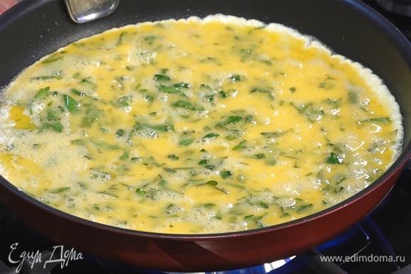 Как только масло растает, вылить на сковороду яичную смесь.
