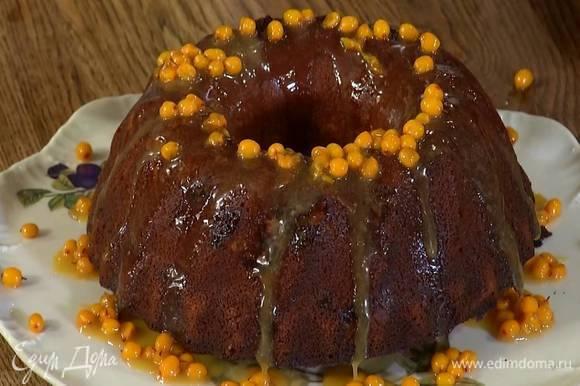 Готовый пирог перевернуть на тарелку и полить половиной облепихового соуса.