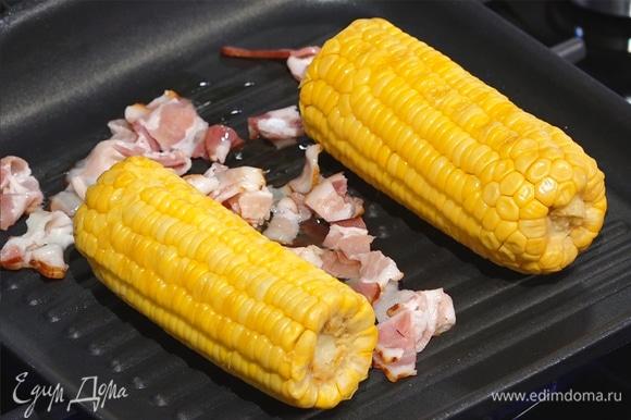 Бекон нарезать тонкими полосками, выложить на сковороду к кукурузе, полить растительным маслом.