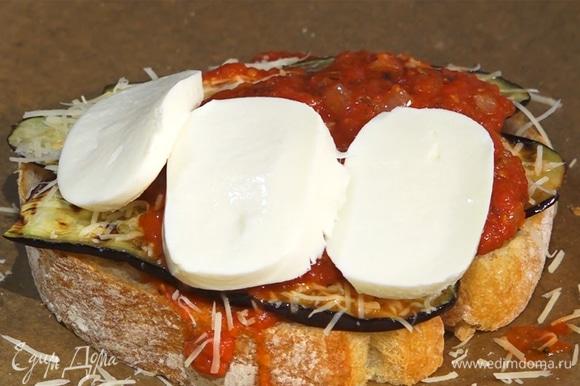 На хлеб выложить слоями ингредиенты: томатный соус, баклажаны, пармезан, снова соус и моцареллу.