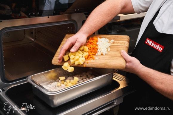 Добавьте овощи к курице, посолите, поперчите, готовьте еще 15 минут.
