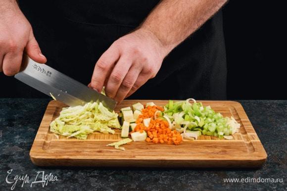 Лук нарежьте полукольцами, сельдерей — средними дольками, морковь нарежьте мелкими кубиками, чеснок мелко порубите, нашинкуйте савойскую капусту. Цукини почистите и нарежьте средними кубиками.