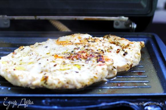 Нагреть гриль. Стряхнуть маринад с курицы и загрилловать филе по 3–4 минуты с каждой стороны до готовности. Дать полежать несколько минут.