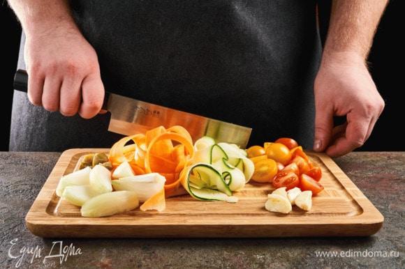 Нарежьте морковь и цукини слайсами, черри и каперсы — пополам, чеснок раздавите, лук крупно нарежьте.