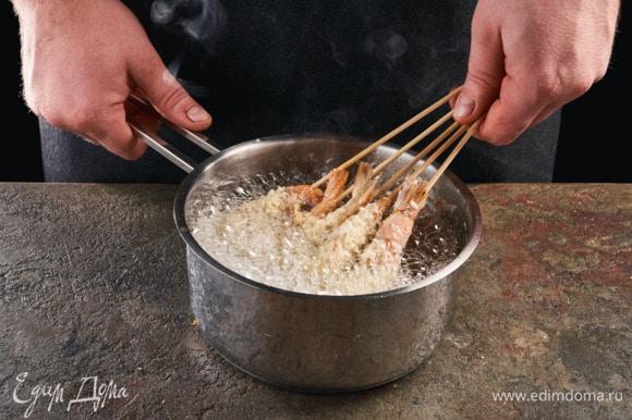 В сотейник налейте растительное масло (по высоте должно быть около 5 см). Разогрейте его. Окунайте креветки в горячее масло. Обжаривайте до золотистого цвета, перевернув один раз, около 3 минут.