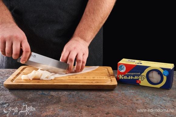 Тушки кальмаров ТМ «Океанрыбфлот» разморозьте, снимите кожу, промойте. Разрежьте тушки напополам и сделайте с внутренней стороны надрезы в виде сетки (будьте аккуратны, чтобы кусочки остались целыми). Затем разделите на полоски по 1 см.