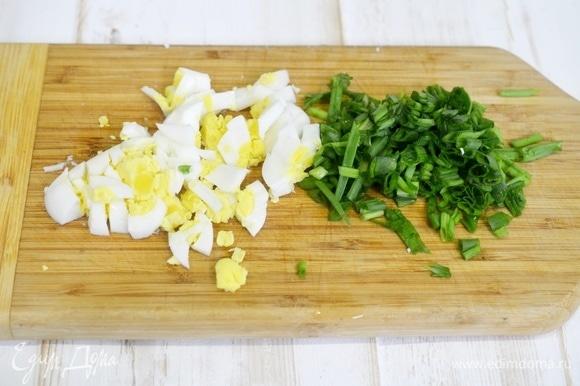 Два яйца отварите вкрутую, лук вымойте. Нарежьте яйцо и лук помельче.