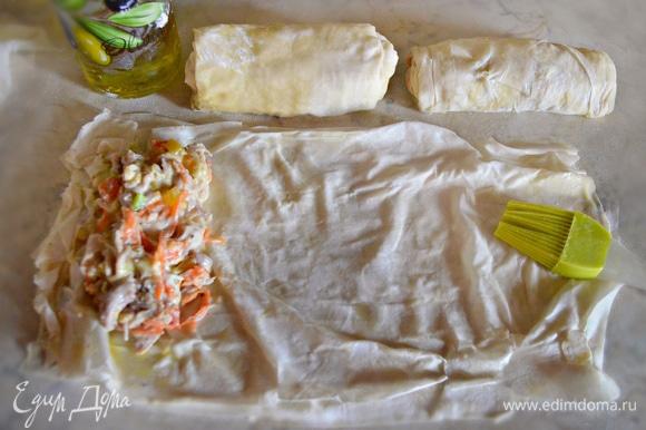 Разложите тесто фило на рабочей поверхности. Каждый лист смажьте растопленным сливочным маслом при помощи кисточки. Сложите стопку из 3–4 листов и разрежьте ее пополам. С краю теста выложите начинку и сверните конвертом, подворачивая края.