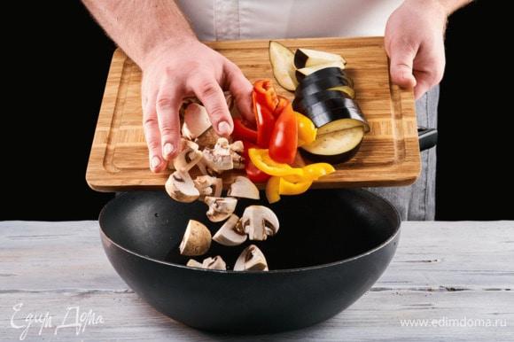 Нарежьте на кусочки болгарский перец, баклажан и грибы, отправьте все на сковороду и обжарьте на растительном масле.