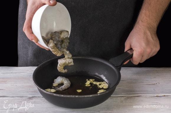На сковороду налейте масло и обжарьте чеснок. Добавьте креветки и обжаривайте до готовности 3 минуты.