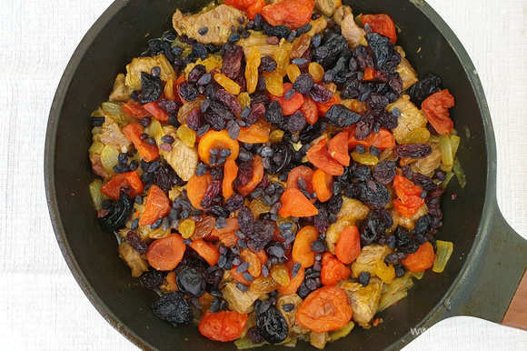 Добавим промытые сухофрукты. Если чернослив и курага крупные, разрежьте их на 2 части. Вольем еще одну столовую ложку масла и обжарим мясо с сухофруктами 2–3 минуты.