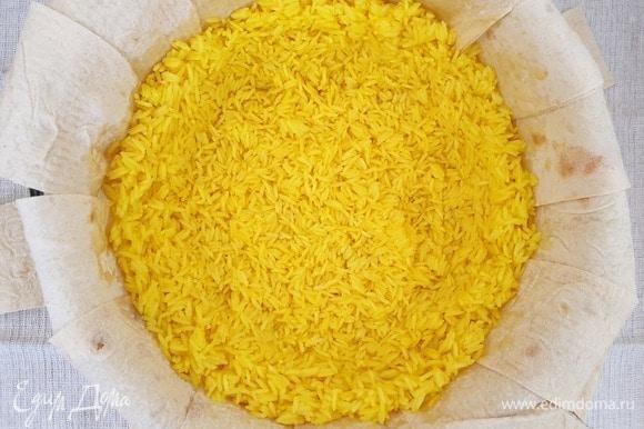Выкладываем на лаваш половину риса. Слегка примнем рис таким образом, чтобы получилась чаша с бортиками. Во время запекания мясо и сухофрукты не должны касаться лаваша.
