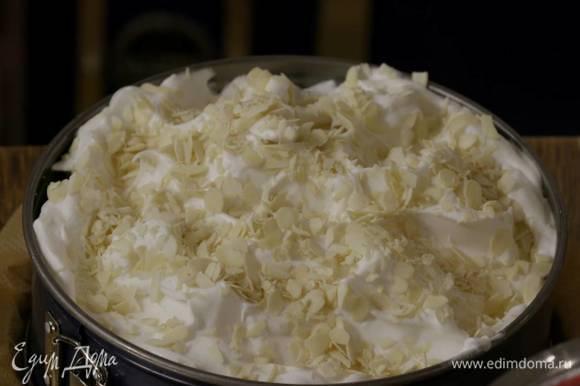 На выпеченный горячий корж выложить в один слой нарезанные сливы, сверху выложить взбитые белки, разровнять и присыпать миндальными хлопьями.