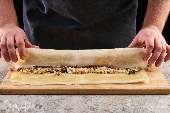Выложите начинку. Сверните рулет и сверху смажьте растопленным сливочным маслом. Выложите рулет на противень, застеленный пекарской бумагой. Выпекайте при 180°С 35–40 минут.