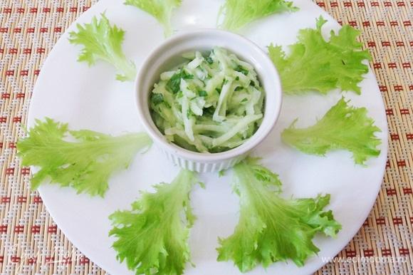 Один из возможных вариантов сервировки: в центр сервировочной тарелки ставим соус и раскладываем листья салата.