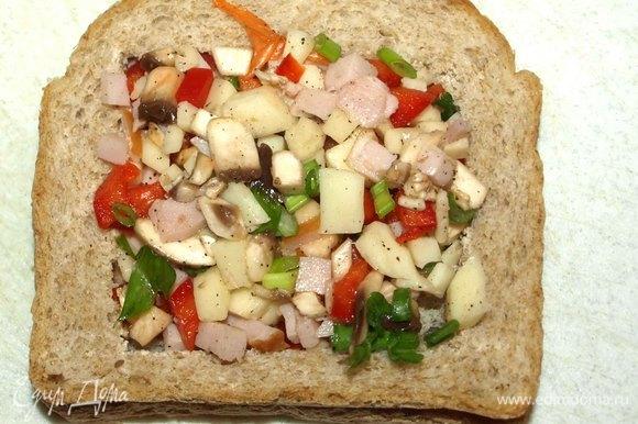 Кладем хлеб с вырезанной серединой на второй кусок. Накладываем начинку.