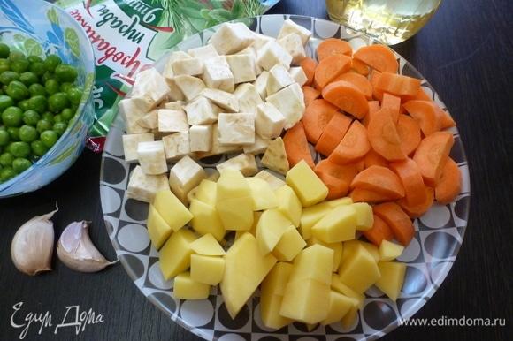 Подготовить овощи для запекания. Все вымыть и почистить. Нарезать кубиком. Чеснок нарезать пластинками. Горошек пока не трогать.