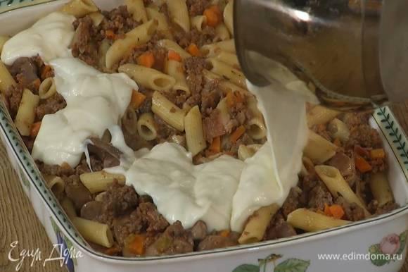 Большую керамическую форму смазать сливочным маслом, посыпать дно оставшимся сыром и выложить пасту, залить все соусом бешамель и запекать в разогретой духовке 30‒40 минут.