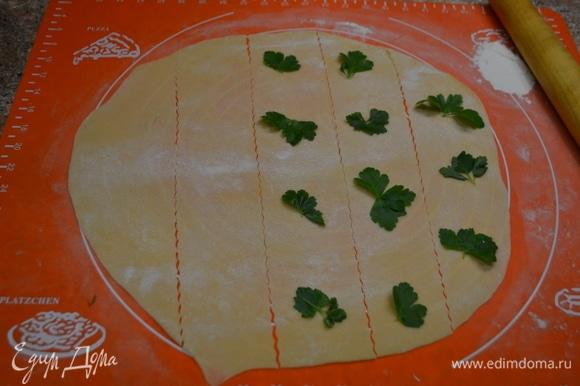 В муку добавляю соль, оливковое масло, яйца, замешиваю тесто. Это долгий процесс. Если желтки оказались недостаточно яркими, можно слегка подкрасить тесто куркумой. Когда тесто станет пластичным, оно готово. На 30 минут убираю его в холодильник. Раскатываю тесто в пласт толщиной 1 мм и нарезаю на полоски. Через полоску выложить листочки зелени так, как показано на фото.