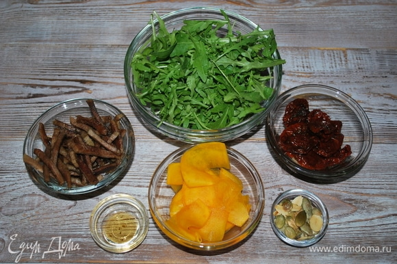 Горсть тыквенных семечек обжарьте, вяленые помидоры нарежьте. Руколу вымойте.