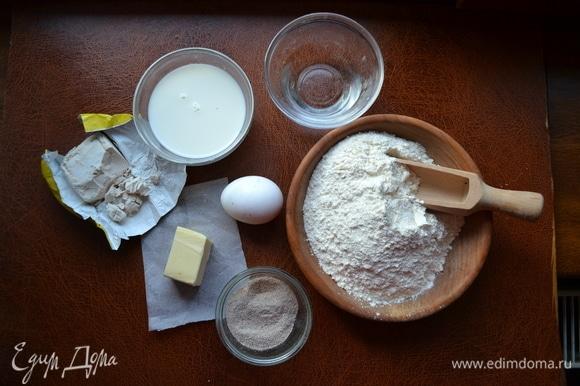 В ведерке хлебопечки смешать молоко, воду, добавить дрожжи. Дрожжи размешать с помощью силиконового венчика. Добавить яйцо, сахар, соль и муку. Начать замес. Через 1–2 минуты добавить мягкое сливочное масло. Замес продолжить в течение 7–10 минут.