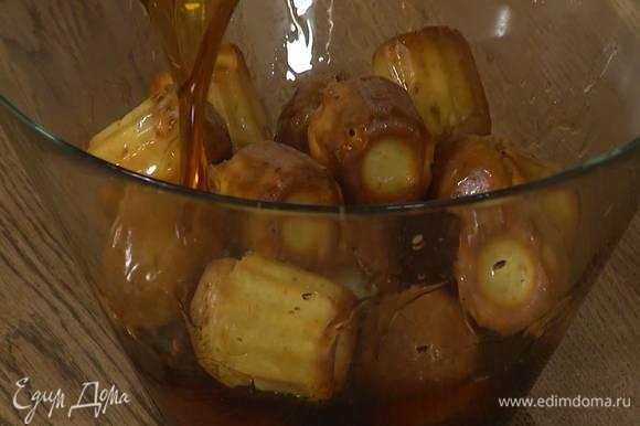 Готовые кексы вынуть из формы, выложить в глубокую миску, залить сиропом и дать пропитаться.