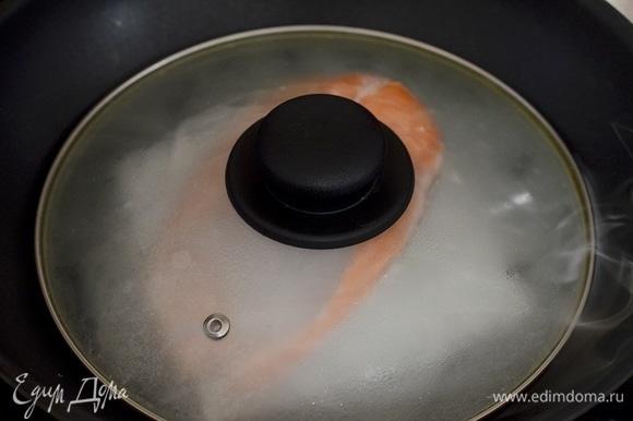 Накройте крышкой. Первые 5–7 минут готовьте на максимальном огне, затем убавьте огонь и готовьте еще минут 10, но следите, чтобы под крышкой был дым. Затем отключите огонь, но оставьте рыбу под крышкой еще минут на 5.
