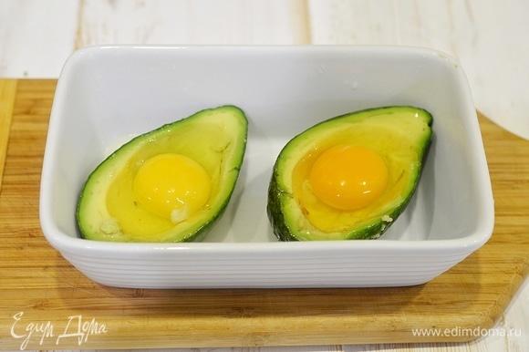 Аккуратно, не повредив желток, вбейте по яйцу в каждую половинку авокадо.