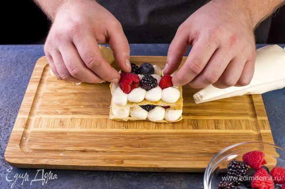 На последний корж выложите крем, украсьте ягодами и веточкой мяты.