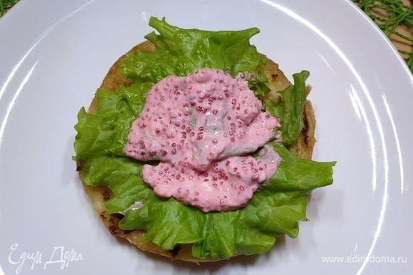 Собираем фишбургер. Булочку разрежем на 2 части. При желании можете обжарить булочку на сковороде гриль. Кладем салатные листья, немного соуса.
