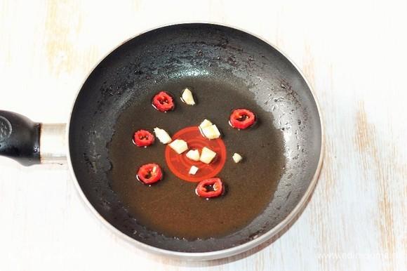 Приготовим медовый соус. На разогретом масле обжариваем порубленный чеснок и нарезанный колечками перец чили до появления аромата. Удаляем овощи из сковороды, масло оставляем.