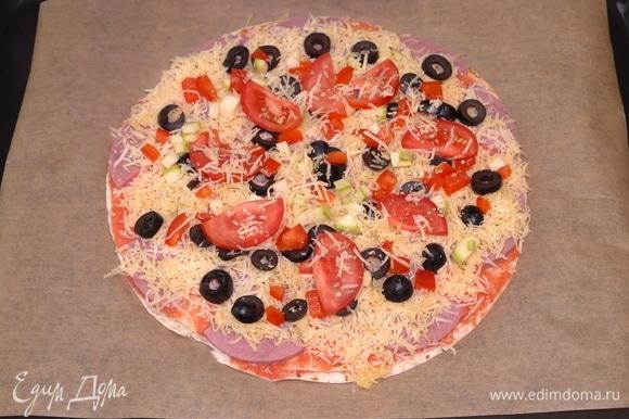 Последний штрих — еще немного сыра, и ставим пиццу в заранее разогретую до 200°C духовку на 20–25 минут.