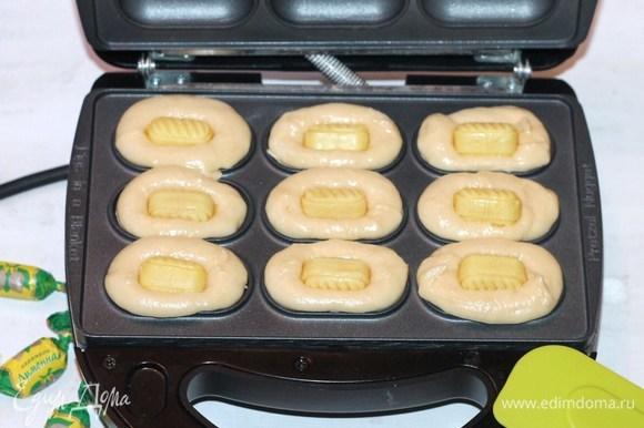 Раскладываем тесто в формочки (не смазываем маслом). Сверху кладем карамель, немного ее утопим в тесте.